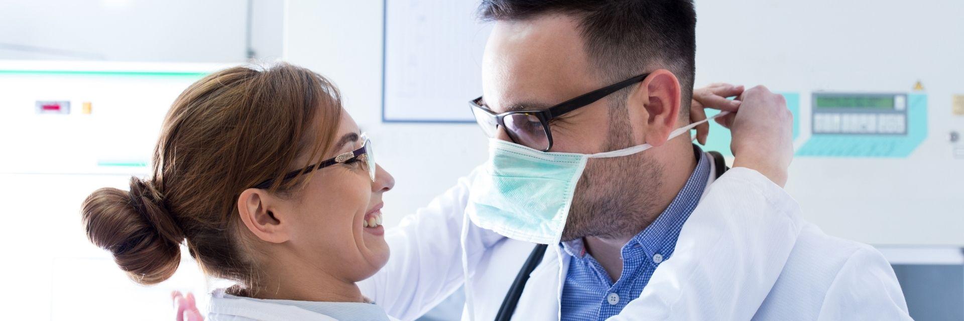Pflegerin bindet Arzt Maske um